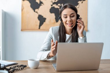 attractive travel agent in headset working near laptop