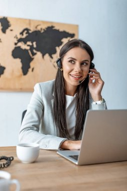 smiling travel agent working near laptop