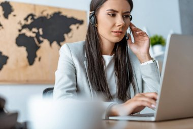 attentive travel agent working near laptop