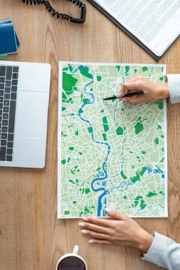 cropped view of travel agent pointing with pen at map on wooden desk