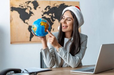 smiling travel agent in santa hat pointing at globe while sitting at workplace