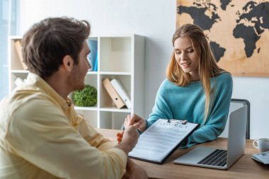 attractive, smiling travel agent showing contract to client