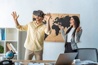 smiling travel agent looking at excited man using vr headset