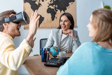 excited young man using vr headset near girlfriend and travel agent