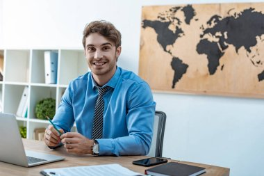 handsome travel agent smiling at camera while sitting at workplace