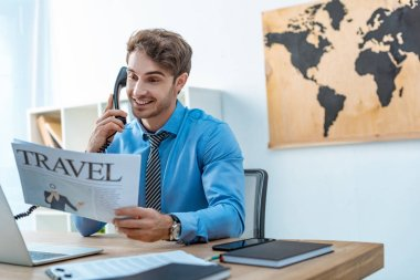 smiling travel agent talking on phone while holding travel newspaper