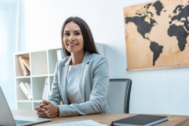 attractive travel agent looking at camera while sitting at workplace