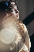 něžná dívka s copánky ve účesu pózuje v bílých boho šaty na šedé s objektivy světlice