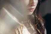 Fotografie oříznutý pohled na boho dívka s copánky ve účesu pózovat v bílých šatech na šedé s objektivem světlice
