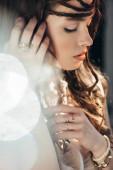 něžné boho dívka s copánky ve stylu pózování na šedé s objektivy světlice