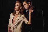 schöner Mann im Anzug umarmt attraktive Frau isoliert auf schwarz
