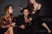Fotografie attraktive Frauen und lächelnder Mann mit Sektgläsern auf schwarzem Grund