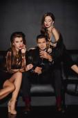 Fotografie attraktive Frauen und gutaussehender Mann mit Champagnergläsern isoliert auf schwarz