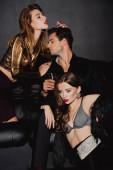 Fotografie attraktive Frauen umarmen gutaussehenden Mann mit Champagnerglas isoliert auf schwarz