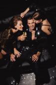Draufsicht auf attraktive und lächelnde Frauen und gutaussehende Männer mit Champagnerglas auf schwarzem Hintergrund