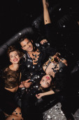 top view of attractive and smiling women and handsome man with champagne glass on black background