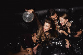 Draufsicht attraktive und lächelnde Frauen mit Discokugel und gutaussehender Mann mit Champagnerglas isoliert auf schwarz