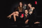 attraktive und lächelnde Freunde mit Discokugel und Plastikbechern auf schwarzem Hintergrund