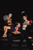 attractive and smiling friends holding disco ball and plastic cups isolated on black