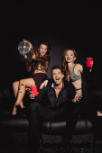 attractive and smiling friends holding disco ball and plastic cups on black background