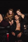 Fotografie attraktive und stilvolle Frauen umarmen gutaussehenden Mann isoliert auf schwarz