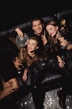 top view of attractive and smiling women with disco ball and handsome man with champagne glass on black background