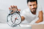 Photo selective focus of bi-racial man holding alarm clock in morning