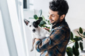 smiling and handsome bi-racial man holding Jack Russell Terrier