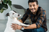 handsome and smiling bi-racial man holding jack russell terrier