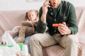 abgeschnittene Ansicht eines Mannes, der auf dem Smartphone spricht und eine Pillen-Blase in der Hand hält, während er neben seiner kranken Tochter sitzt
