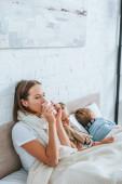 Kranke Frau niest in Serviette, während sie neben kranken Kindern im Bett sitzt