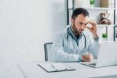 pozorný lékař při pohledu na notebook, zatímco sedí na pracovišti