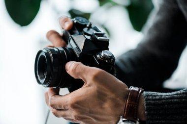 Cropped view of bi-racial man holding digital camera in apartment stock vector