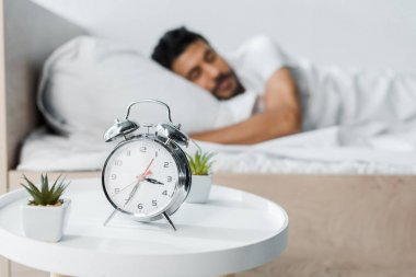 Selective focus of alarm clock, plants and handsome bi-racial man sleeping on background stock vector