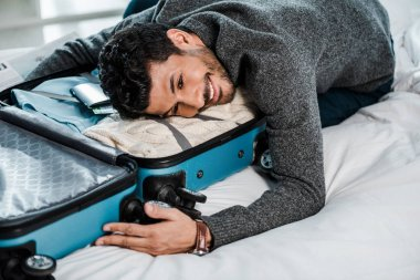 Handsome and smiling bi-racial man lying on travel bag stock vector