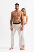 sinnliche Frau umarmt hemdlosen Oberkörper des Mannes auf weiß