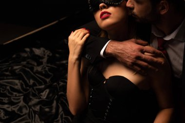 cropped view of sexy man hugging woman in mask on bed in dark room