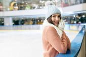 pozitív lány pulóverben, sál, kesztyű és kalap álló korcsolyapálya