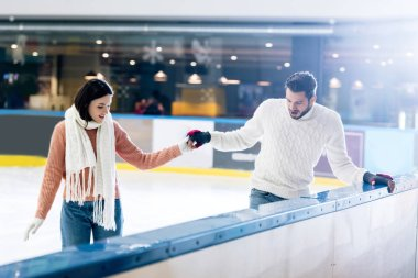 Cheerful young woman teaching man to skate on a rink while holding hands stock vector