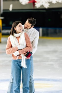 Happy young couple in sweaters hugging on skating rink stock vector