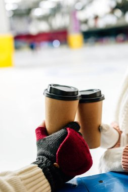 Cropped view of couple holding disposable cups of coffee to go on skating rink stock vector