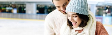 Panoramic shot of excited couple spending time on skating rink stock vector