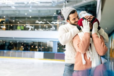 Handsome boyfriend closing eyes to girlfriend to make a surprise on skating rink stock vector