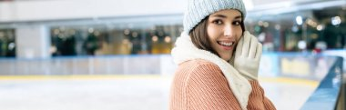 Panoramic shot of cheerful attractive girl in sweater, scarf, gloves and hat standing on skating rink stock vector