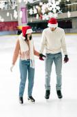 šťastný pár v Santa klobouky drží za ruce, zatímco bruslení na kluzišti