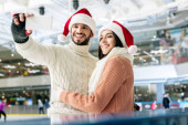 Fotografie beautiful cheerful couple in santa hats taking selfie on smartphone on skating rink at christmastime