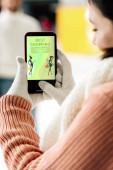 Kijev, Ukrajna - november 15, 2019: vágott kilátás nő kesztyűben gazdaság okostelefon a legjobb bevásárló app a képernyőn