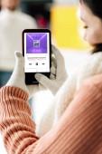 Kijev, Ukrajna - november 15, 2019: vágott kilátás nő kesztyűben gazdaság okostelefon zenei alkalmazás a képernyőn