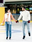 gyönyörű boldog pár fogja egymás kezét és időt töltenek a korcsolyapályán