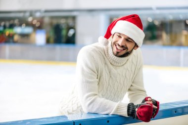 Happy man in sweater and santa hat on skating rink stock vector